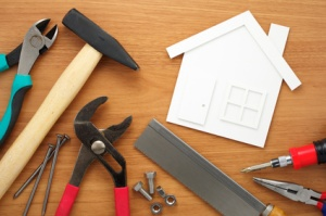 Home planning and preparing. House shaped paper cutout and tools on wooden table.