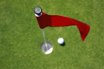 Golfball on green with red flag.